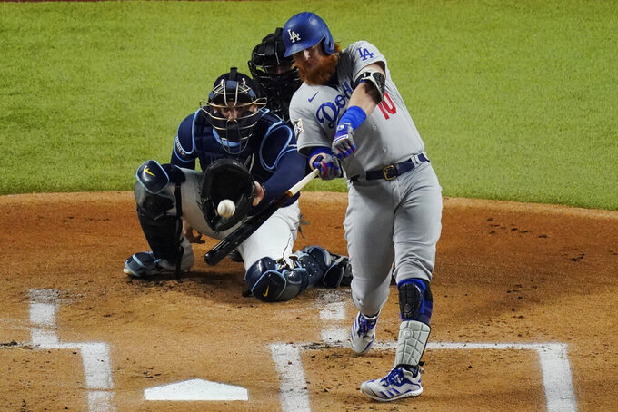 """FILE - In this Oct. 24, 2020, file photo, Los Angeles Dodgers' Justin Turner hits a home run against the Tampa Bay Rays during the first inning in Game 4 of the baseball World Series in Arlington, Texas. Turner is returning to the Dodgers, announcing via Twitter that he's ready to """"run it back"""" with the World Series champions. (AP Photo/Sue Ogrocki, File)"""
