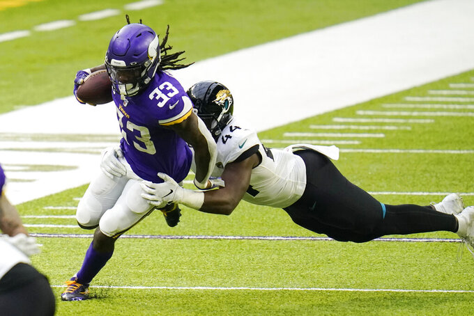 Minnesota Vikings running back Dalvin Cook (33) runs from Jacksonville Jaguars linebacker Myles Jack (44) during the second half of an NFL football game, Sunday, Dec. 6, 2020, in Minneapolis. (AP Photo/Jim Mone)