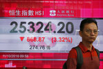 A man walks past an electronic board showing Hong Kong share index outside a bank In Hong Kong, Thursday, Oct. 11, 2018. Asian markets tumbled on Thursday, after Wall Street slumped on a heavy selling of technology and internet stocks. (AP Photo/Kin Cheung)