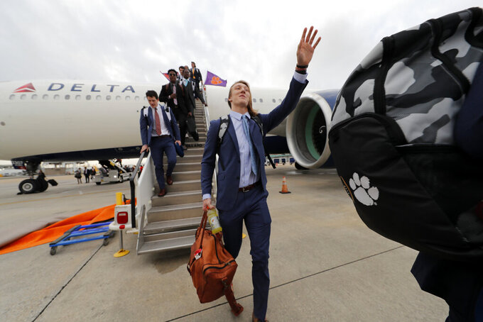 Clemson quarterback Trevor Lawrence waves as he arrives with the team for the NCAA College Football Playoff title game in New Orleans, Friday, Jan. 10, 2020. Clemson is scheduled to play LSU on Monday. (AP Photo/Gerald Herbert)