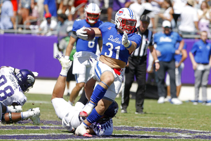 SMU running back Tyler Lavine (31) runs out of an attempted tackle by TCU linebacker Wyatt Harris during the second half of an NCAA football game in Fort Worth, Texas, Saturday, Sept. 25, 2021. (AP Photo/Michael Ainsworth)