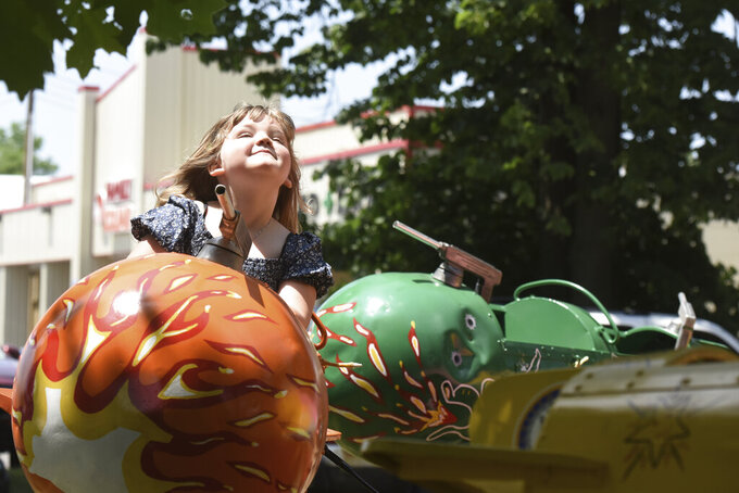 Leah Massey, 5, of Coloma, Mich., enjoys the sunshine as she takes a spin on one of the carnival rides Friday, June 11, 2021, during the opening of the Hartford Strawberry Festival, held at Ely Park in downtown Hartford, Mich.(Don Campbell/The Herald-Palladium via AP)