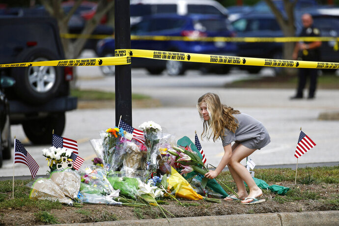 FILE - In this June 1, 2019 file photo,  a girl leaves flowers at a makeshift memorial at the edge of a police cordon in front of a municipal building that was the scene of a shooting, in Virginia Beach, Va. An independent probe into Virginia Beach's mass shooting failed to offer clear answers as to why a city engineer opened fire in his workplace, the findings released Wednesday, Nov. 13, showed. (AP Photo/Patrick Semansky, File)