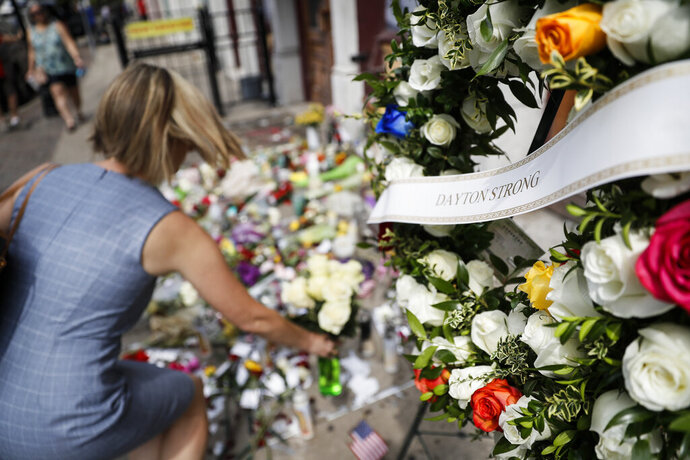 Mourners bring flowers to a makeshift memorial Tuesday, Aug. 6, 2019, for the slain and injured in the Oregon District after a mass shooting that occurred early Sunday morning, in Dayton. (AP Photo/John Minchillo)