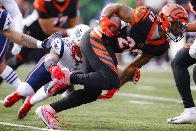 Cincinnati Bengals running back Joe Mixon (28) runs the ball against New England Patriots strong safety Patrick Chung, left, in the first half of an NFL football game, Sunday, Dec. 15, 2019, in Cincinnati. (AP Photo/Gary Landers)