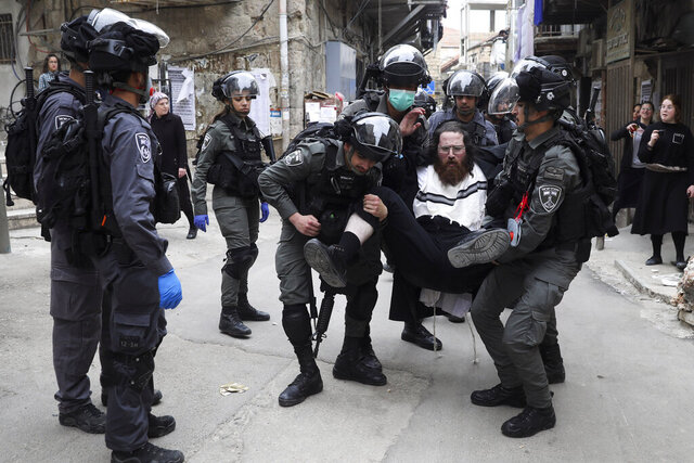 Israeli police arrest an ultra-Orthodox Jewish man during protest against government's measures to stop the spread of the coronavirus, in the Mea Shearim neighborhood of Jerusalem, on Monday, March 30, 2020. (AP Photo/Mahmoud Illean)