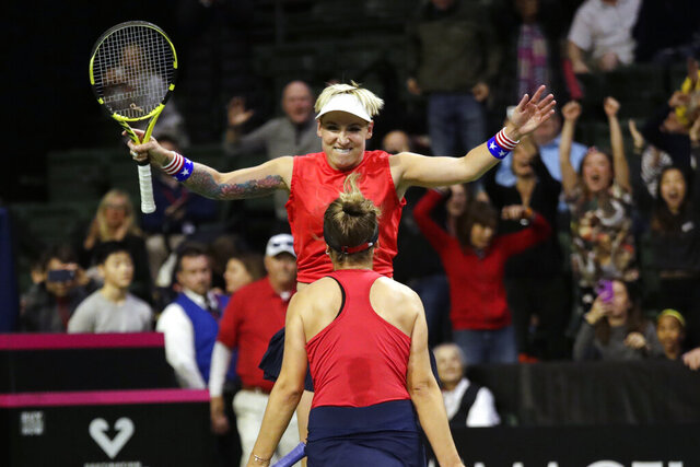 United States' Bethanie Mattek-Sands leaps toward Sofia Kenin after they defeated Latvia's Jelena Ostapenko and Anastasija Sevastova during the doubles match in a Fed Cup tennis qualifying tie to advance the U.S. team Saturday, Feb. 8, 2020, in Everett, Wash. (AP Photo/Elaine Thompson)