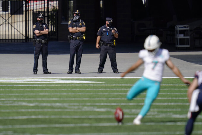 Police officers wear masks on the sideline as Miami Dolphins place kicker Jason Sanders (7) kicks off to the New England Patriots in the first half of an NFL football game during the coronavirus pandemic, Sunday, Sept. 13, 2020, in Foxborough, Mass. (AP Photo/Charles Krupa)