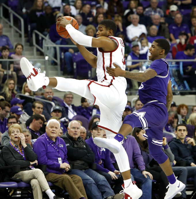 Oklahoma guard Christian James (0) jumps for a pass in front of TCU guard Kendric Davis (5) during the first half of an NCAA college basketball game in Fort Worth, Texas, Saturday, Feb. 16, 2019. (AP Photo/LM Otero)