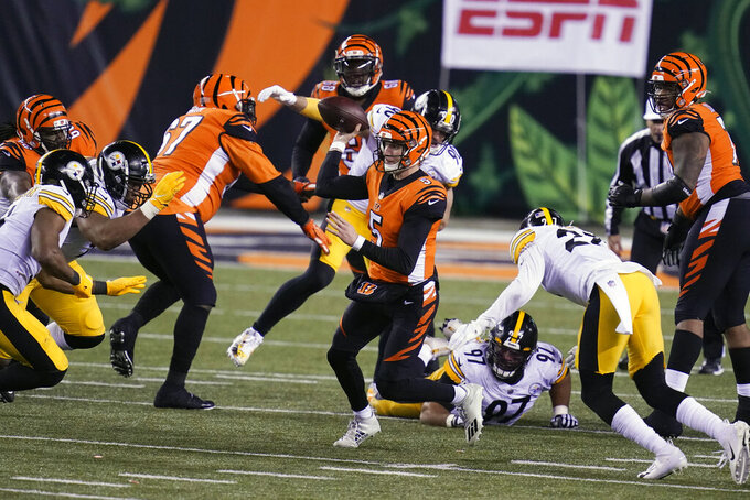 Cincinnati Bengals quarterback Ryan Finley (5) scrambles to throw during the second half of an NFL football game against the Pittsburgh Steelers, Monday, Dec. 21, 2020, in Cincinnati. (AP Photo/Michael Conroy)