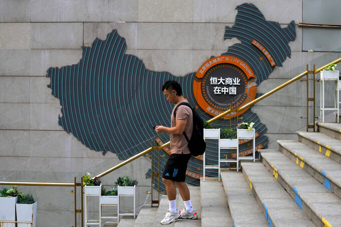 A man walks by a map showing Evergrande development projects in China, at an Evergrande city plaza in Beijing, Wednesday, Sept. 15, 2021. One of China's biggest real estate developers is struggling to avoid defaulting on billions of dollars of debt, prompting concern about the broader economic impact and protests by apartment buyers about delays in completing projects. Rating agencies say Evergrande Group appears likely to be unable to repay all of the 572 billion yuan ($89 billion) it owes banks and other bondholders. That might jolt financial markets, but analysts say Beijing is likely to step in to prevent wider damage. (AP Photo/Andy Wong)
