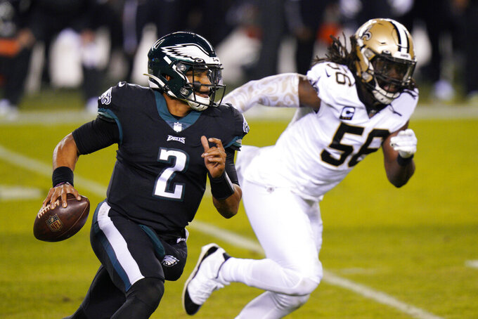 Philadelphia Eagles' Jalen Hurts, left, scrambles past New Orleans Saints' Demario Davis during the first half of an NFL football game against the New Orleans Saints, Sunday, Dec. 13, 2020, in Philadelphia. (AP Photo/Chris Szagola)
