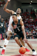 Cincinnati guard Mika Adams-Woods (3) drives past Houston center Brison Gresham during the first half of an NCAA college basketball game Sunday, March 1, 2020, in Houston. (AP Photo/Michael Wyke)