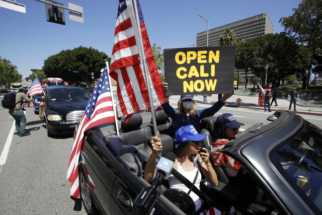 Protesters drive by in a convertible car during a rally calling for an end to California Gov. Gavin Newsom's stay-at-home orders amid the COVID-19 pandemic, Wednesday, April 22, 2020, outside of City Hall in downtown Los Angeles. (AP Photo/Marcio Jose Sanchez)