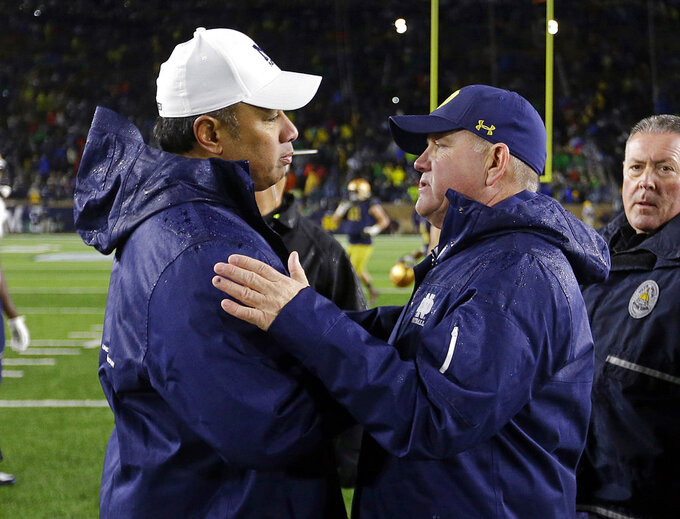 FILE - In this Nov. 18, 2017, file photo, Notre Dame head coach Brian Kelly, right, greets Navy head coach Ken Niumatalolo following an NCAA college football game in South Bend, Ind. No. 3 Notre Dame faces Navy on Saturday in San Diego.  (AP Photo/Michael Conroy, File)