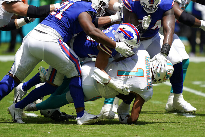 Miami Dolphins quarterback Tua Tagovailoa (1) is sacked by Buffalo Bills strong safety Micah Hyde (23) during the first half of an NFL football game, Sunday, Sept. 19, 2021, in Miami Gardens, Fla. (AP Photo/Wilfredo Lee)