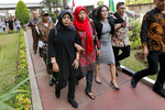 Baiq Nuril Maknun, second from left in red, walks toward the Attorney General's office in Jakarta, Indonesia. Friday, July 12, 2019. Maknun facing six month in prison in Indonesia for recording her boss's sexual harassment is expected to receive a presidential amnesty after an outcry over the sentence. Attorney-General Muhammad Prasetyo said Friday he suspended enforcement of the sentence and a 500 million rupiah ($35,000) fine that was recently upheld by the Supreme Court. (AP Photo/Tatan Syuflana)