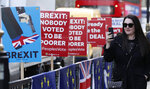 A woman takes pictures on her smart phone as she walks past anti-Brexit placards near the House of Parliament in London, Tuesday, March 26, 2019. British Prime Minister Theresa May's government says Parliament's decision to take control of the stalled process of leaving the European Union underscores the need for lawmakers to approve her twice-defeated deal. (AP Photo/Alastair Grant)