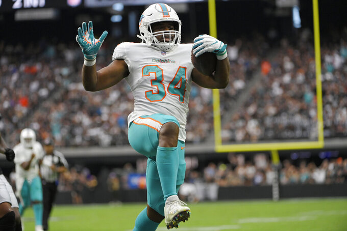 Miami Dolphins running back Malcolm Brown (34) scores a touchdown against the Las Vegas Raiders during the first half of an NFL football game, Sunday, Sept. 26, 2021, in Las Vegas. (AP Photo/David Becker)