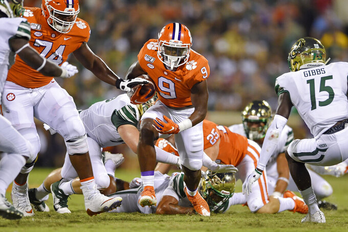 Clemson's Travis Etienne (9) rushes out of the backfield with blocking help from John Simpson (74) while Charlotte's Marquavis Gibbs defends during the first half of an NCAA college football game Saturday, Sept. 21, 2019, in Clemson, S.C. (AP Photo/Richard Shiro)