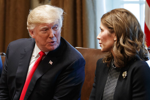 FILE - In this Dec. 12, 2018 file photo, President Donald Trump speaks to then-Gov.-elect Kristi Noem, R-S.D., during a meeting at White House in Washington. At the governor's request, the South Dakota Department of Tourism aired a Fox News ad narrated by Gov. Noem that premiered alongside her speech at the Republican National Convention. The 30-second spot, which cost taxpayers $819,000, advertises the state as a place open for visitors despite the coronavirus pandemic. (AP Photo/Evan Vucci File)