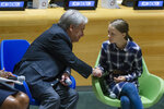 FILE - In this Saturday, Sept. 21, 2019 file photo Swedish environmental activist Greta Thunberg, right, shakes hands with U.N. Secretary-General Antonio Guterres, during the Youth Climate Summit at United Nations headquarters. In a wide-ranging monologue on Swedish public radio, teenage climate activist Greta Thunberg recounts how world leaders queued up to have their picture taken with her even as they shied away from acknowledging the grim scientific fact that time is running out to curb global warming. (AP Photo/Eduardo Munoz Alvarez, file)