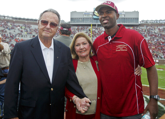 FILE - In this Nov. 16, 2013, file photo, former Florida State head coach Bobby Bowden, left, his wife Ann, center, and former FSU quarterback Charlie Ward pose before an NCAA college football game against Syracuse in Tallahassee, Fla. Bowden, the folksy Hall of Fame coach who built Florida State into an unprecedented college football dynasty, has died. He was 91. Bobby's son, Terry, confirmed to The Associated Press that his father died at home in Tallahassee, Fla., surrounded by family early Sunday, Aug. 8, 2021. (AP Photo/Phil Sears, File)