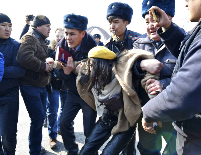 Kyrgyz policemen detain an activist of the Femen women's rights movement at Victory Square during celebration of the International Women's Day in Bishkek, Kyrgyzstan, Sunday, March 8, 2020. (AP Photo/Vladimir Voronin)