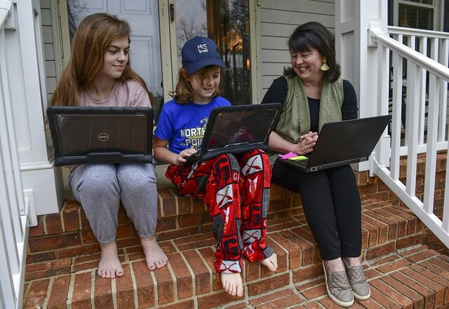 Catherine Gray, left, a sophomore at TL Hanna, Lucy Gray, a fifth grader from North Pointe Elementary and Lani Gray study with laptops in Anderson on Monday, March 16, 2020. (Ken Ruinard/The Independent-Mail via AP)