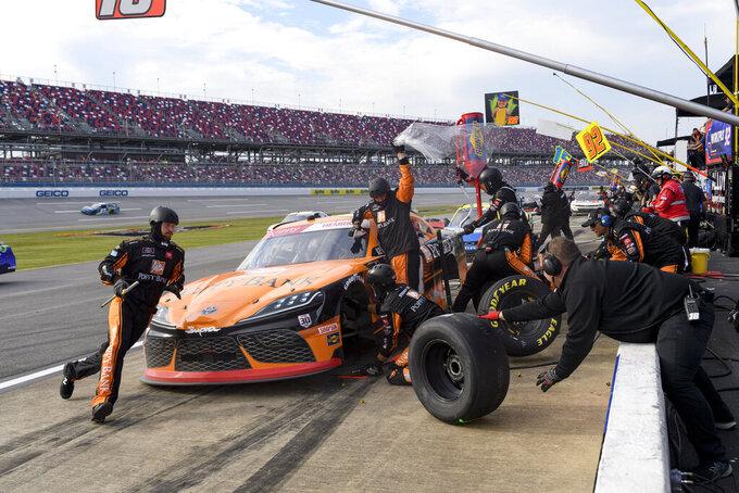 Crew members work a pit stop by Daniel Hemric during a NASCAR Xfinity Series auto race Saturday, Oct. 2, 2021, in Talladega, Ala. (AP Photo/John Amis)