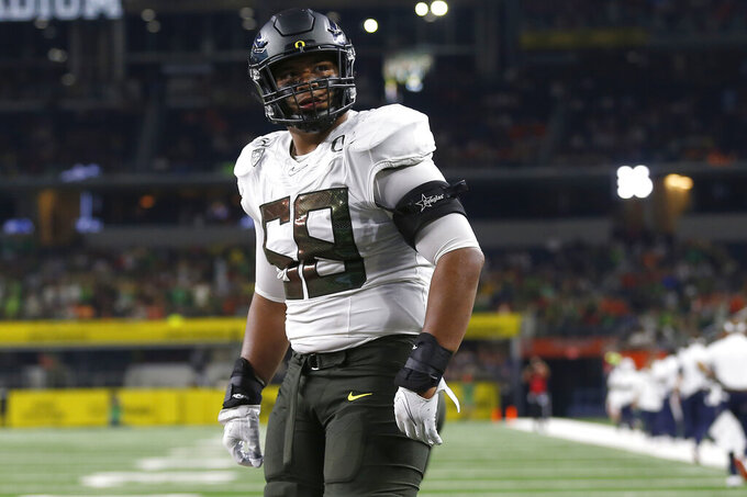 FILE - In this Aug. 31, 2019, file photo, Oregon offensive lineman Penei Sewell (58) looks on as Oregon plays Auburn in an NCAA college football game, in Arlington, Texas. Penn State linebacker Micah Parsons and Oregon tackle Penei Sewell are among 11 players selected to The Associated Press preseason All-America first-team, Tuesday, Aug. 25, 2020, who are not slated to play this fall. (AP Photo/Ron Jenkins, File)