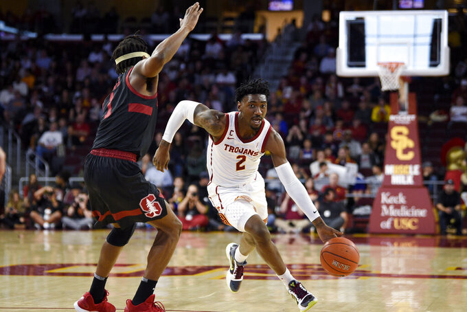 Southern California guard Jonah Mathews, right, drives to the basket while Stanford guard Daejon Davis defends during the first half of an NCAA college basketball game in Los Angeles, Saturday, Jan. 18, 2020. (AP Photo/Kelvin Kuo)
