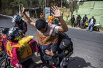 A police stops a motorcyclist to search him at a security checkpoint in the El Milagro area of the Mixco municipality on the outskirts of Guatemala City, Friday, Jan. 17, 2020. Guatemala's new president announced a state of alert for two municipalities with high crime rates to combat gang activity Friday, a measure that allows the deployment of military troops. (AP Photo/Oliver de Ros)