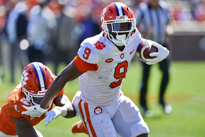 "FILE - In this April 6, 2019, file photo, Clemson's Travis Etienne (9) rushes out of the tackle attempt by Derion Kendrick during Clemson's annual Orange and White NCAA college football spring scrimmage in Clemson, S.C. Sure, Clemson lost all four of its ""Power Rangers"" defensive line and seven starters on defense from its title team. But the Tigers' offense, led by Heisman Trophy candidates quarterback Trevor Lawrence and tailback Travis Etienne, looks ready to operate at an even higher level than a year ago when it averaged 527 yards and 44.3 points a game.  (AP Photo/Richard Shiro, File)"