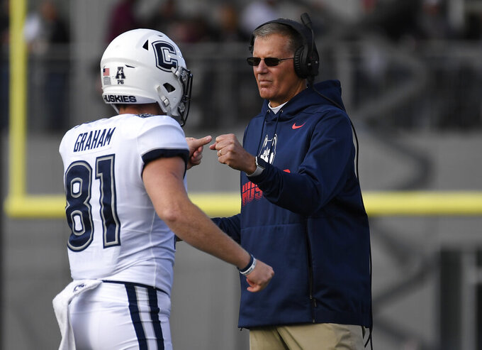 Connecticut head coach Randy Edsall, right, bumps fists with Connecticut punter Brett Graham (81) during the first half of an NCAA college football game against Massachusetts, Saturday, Oct. 26,, 2019, in Amherst, Mass. (AP Photo/Jessica Hill)