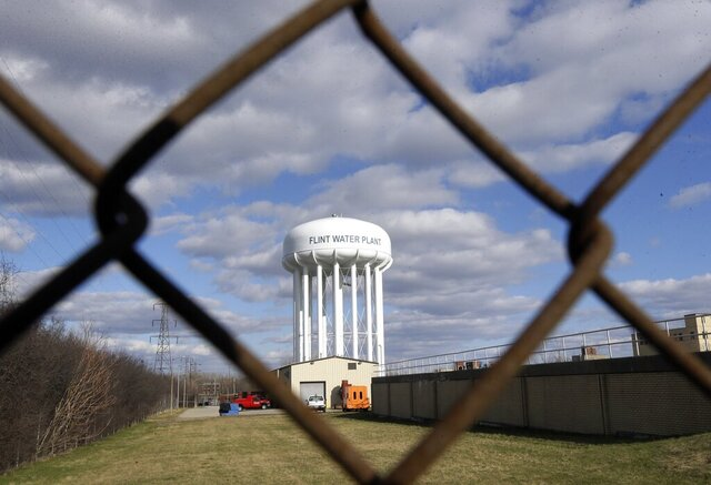 FIL - In this March 21, 2016, file photo the Flint Water Plant water tower is seen in Flint, Mich. Michigan Gov. Gretchen Whitmer says a proposed $600 million deal between the state of Michigan and Flint residents harmed by lead-tainted water is a step toward making amends. Officials announced the settlement Thursday, Aug. 20, 2020, which must be approved by a federal judge. (AP Photo/Carlos Osorio, File)