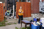 Kristen Bigogno stands on the sidewalk after being evicted from her home Friday, Sept. 17, 2021, in St. Louis. Bigogno is among thousands of Americans facing eviction now that the national moratorium has ended. (AP Photo/Jeff Roberson)