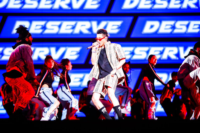 Singer Kris Wu, center, performs in the 2017 Tmall 11.11 Global Shopping Festival gala, in Shanghai, China on Nov. 10, 2017. The popular Chinese-Canadian singer, Kris Wu, has lost endorsement deals with at least 10 brands including Porsche and Louis Vuitton after a teen-ager accused him of having sex with her while she was drunk. (Chinatopix via AP)