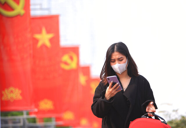 A woman wearing face mask looks at her phone in Hanoi, Vietnam, Jan. 23, 2021. Vietnam has reported 84 new cases of local transmission after nearly two months. Vietnam has reported 82 new COVID-19 cases in two clusters, hours after counting its first new local cases in nearly two months. (AP Photo/Hau Dinh)