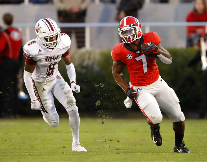 Georgia running back D'Andre Swift (7) rushes for a first down as Massachusetts cornerback Isaiah Rodgers (9) chases him during the first half of an NCAA college football game Saturday, Nov. 17, 2018, in Athens, Ga. Georgia won 66-27. (AP Photo/John Bazemore)