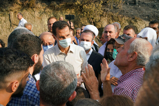 In this photo released Tuesday, Oct. 13, 2020 on the official Facebook page of the Syrian Presidency, Syrian President Bashar Assad, center, wearing a mask to help prevent the spread of the coronavirus, speaks with people during his visit to the coastal province of Latakia, Syria. Assad made a rare public visit to Latakia where he toured areas that suffered heavy damage in last week's deadly wildfires. (Syrian Presidency via Facebook via AP)