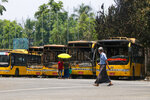 People look at a row of burnt public transport buses parked at Kyimyindaing township in Yangon, Myanmar Monday, April 12, 2021.  Local news media reported that the buses got burned early Monday morning, but provided no details for the cause. (AP Photo)