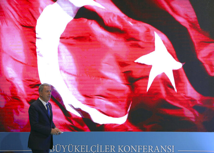 Turkey's Defense Minister Hulusi Akar addresses a meeting of his country's ambassadors, in Ankara, Turkey, Wednesday, Aug. 7, 2019. Akar says his country would like to establish a safe zone in northeast Syria jointly with the United States but would act alone if necessary.(Turkish Defence Ministry via AP, Pool)