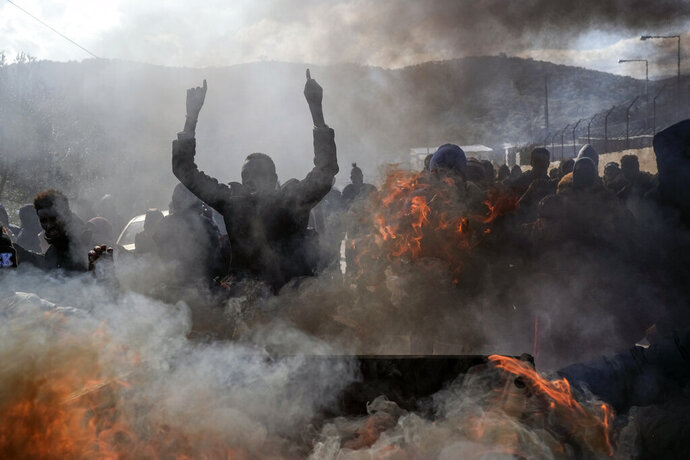 Refugees and migrants burn garbage bins and chant slogans as they demonstate outside Moria camp, following the stabbing death of an 20-year-old man from Yemen in the Greek island of Lesbos, Friday, Jan, 17, 2020. Authorities arrested a 27-year-old Afghan migrant in connection with the incident. Overcrowding at Moria has steadily worsened over the past year as the number of arrivals of migrants and refugees using clandestine routes from Turkey to the Greek islands remains high _ and totaled nearly 60,000 in 2019. (AP Photo/Aggelos Barai)