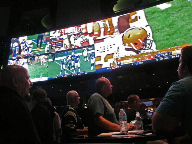 FILE — In this Sept. 9, 2018 file photo, customers watch an NFL game in a sports betting lounge, in Atlantic City, N.J. New Jersey's top gambling regulator is threatening to fine sports books operating in his state that ask customers to cancel requests to cash out money from their accounts, saying the practice is ongoing and