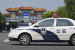"""A police car passes by the entrance into the Tianjin Binhai No. 1 Hotel where U.S. and Chinese officials are holding talks in the Tianjin municipality in China on Monday, July 26, 2021. China blamed the U.S. for what it called a """"stalemate"""" in bilateral relations as high-level face-to-face talks began Monday in the Chinese city of Tianjin.  (AP Photo/Ng Han Guan)"""