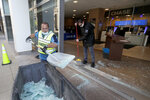 Clean up crews at a Chase Bank branch remove shattered glass early Sunday morning, May 31, 2020, in Chicago, after a night of unrest and protests over the death of George Floyd, a black man who was in police custody in Minneapolis. Floyd died after being restrained by Minneapolis police officers on Memorial Day. (AP Photo/Charles Rex Arbogast)