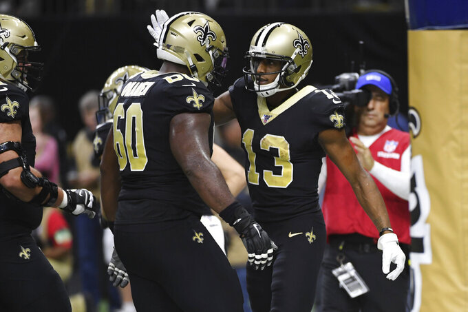 New Orleans Saints offensive guard Patrick Omameh (60) congratulates wide receiver Michael Thomas (13) after Thomas scored a touchdown, during the second half at an NFL football game against the Carolina Panthers, Sunday, Nov. 24, 2019, in New Orleans. (AP Photo/Bill Feig)