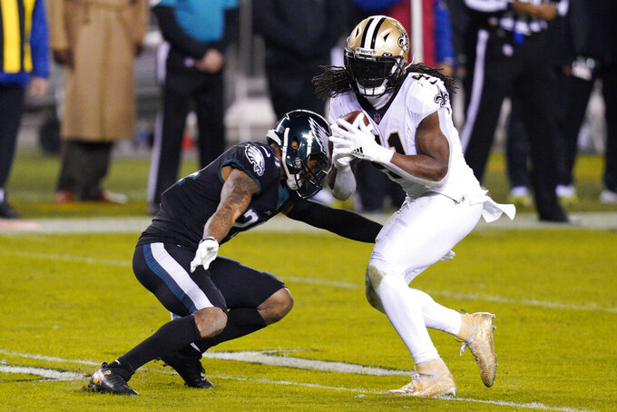 New Orleans Saints' Alvin Kamara (41) is tackled by Philadelphia Eagles' Darius Slay (24) during the second half of an NFL football game, Sunday, Dec. 13, 2020, in Philadelphia. (AP Photo/Chris Szagola)