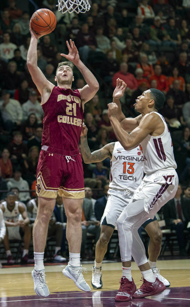 Boston College forward Nik Popovic (21) shoots a basket against Virginia Tech forward Kerry Blackshear Jr. (24) and Virginia Tech guard Ahmed Hill (13) during the first half of an NCAA college basketball game Saturday, Jan. 5, 2019, in Blacksburg, Va. (AP Photo/Don Petersen)